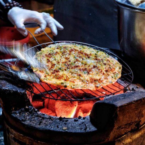 Thưởng thức bánh tráng hành nóng hổi tại chợ đêm Đà Lạt.