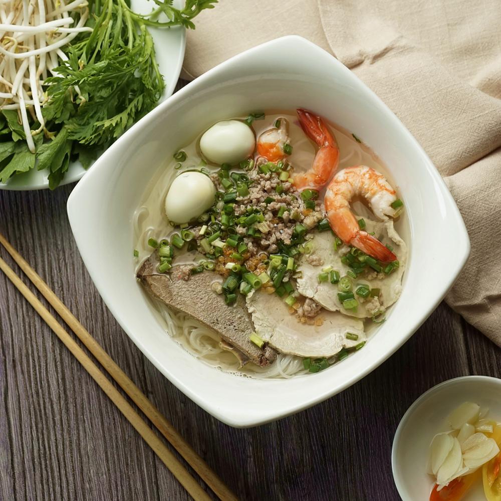 """Hủ tiếu Nam Vang tại Bùi Văn Ngọ thơm lừng với phần """"topping"""" phong phú: trứng cút, tôm, thịt..., với dĩa rau ăn kèm tươi xanh, đi cùng tỏi và ớt ngâm giấm đúng điệu."""